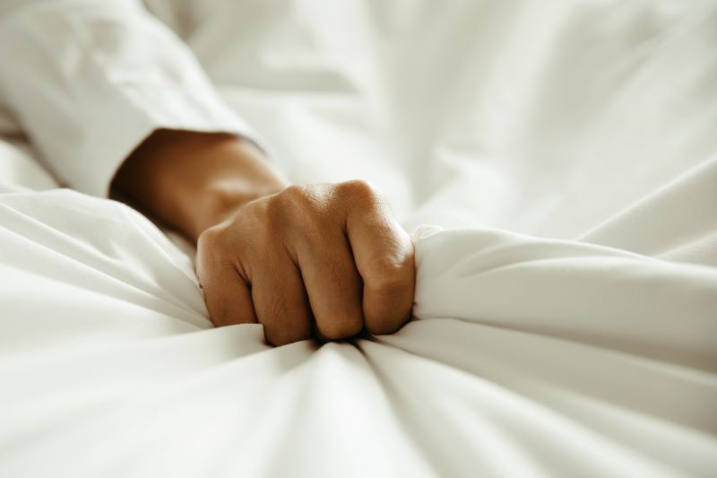 Close up of hand gripping bed sheets
