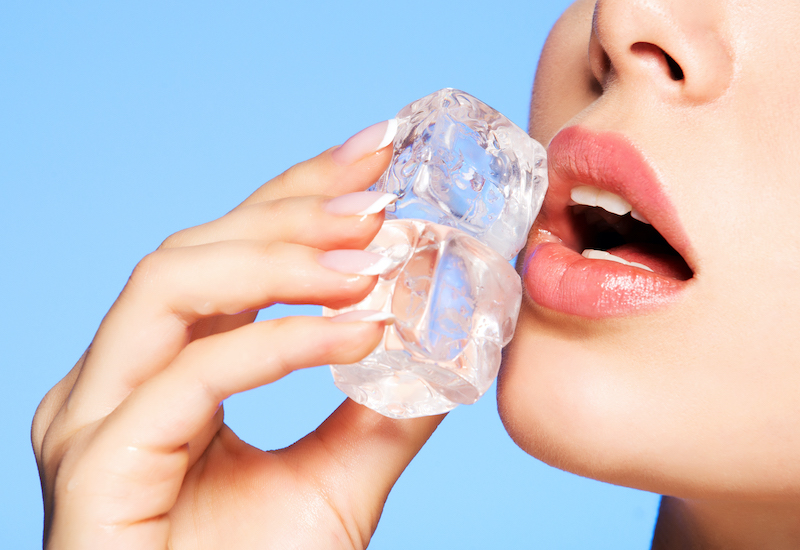 Close up of a woman applying ice to her face