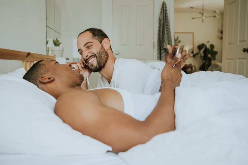Couple chatting and smiling in bed