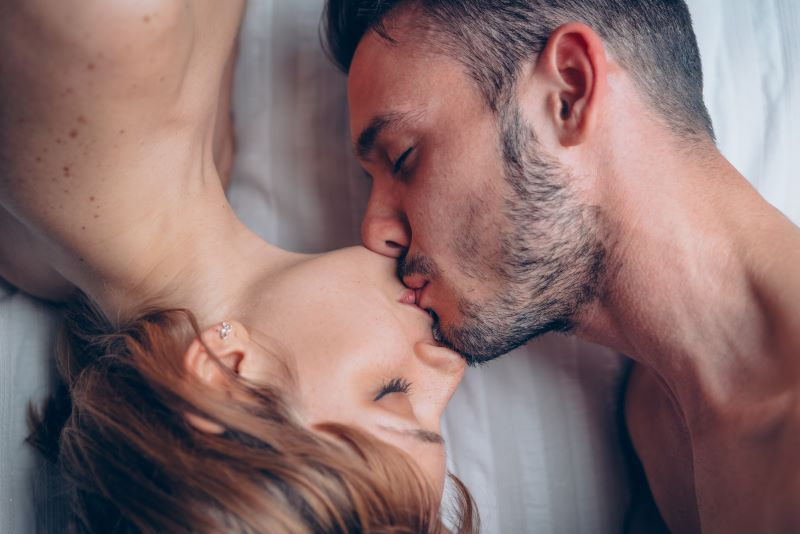 Couple having romantic kiss in bed