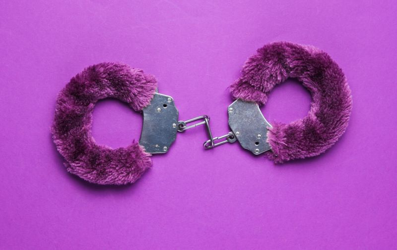 Purple fluffy handcuffs on purple background