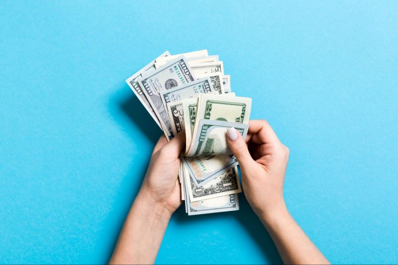Hand counting dollar bills on blue background