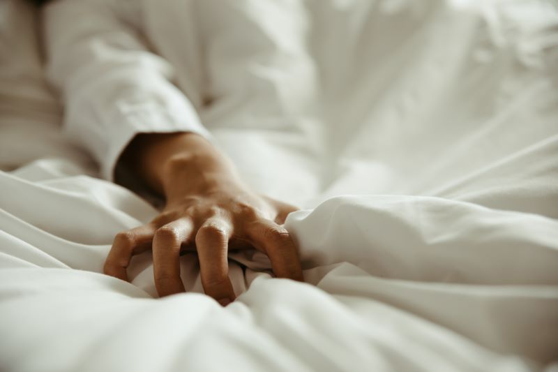Hand gripping white bed sheet