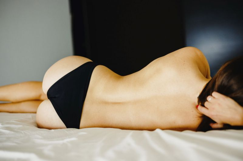 Back of woman on bed in panties
