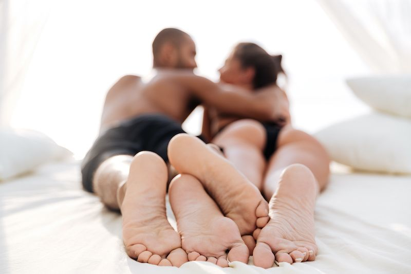 Back view and feet of young couple embracing in bed