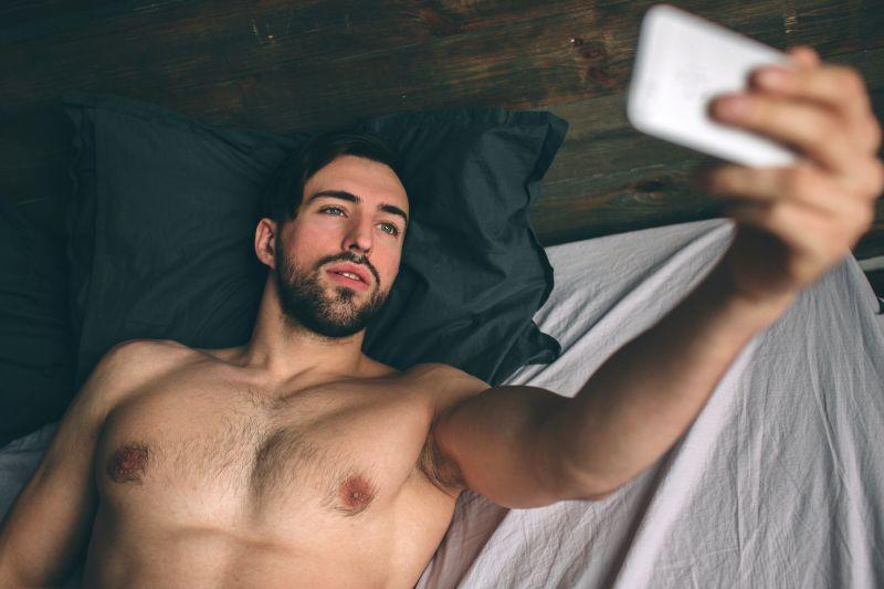 Bearded man taking selfie in bed