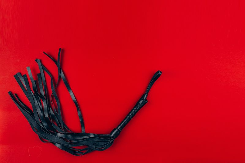Black flogger on red background