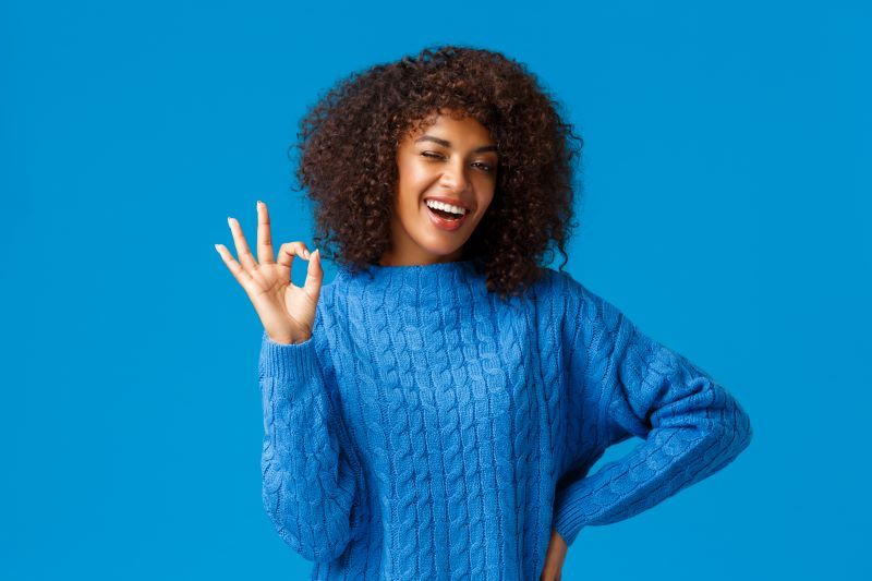 Cheerful young woman making Okay sign