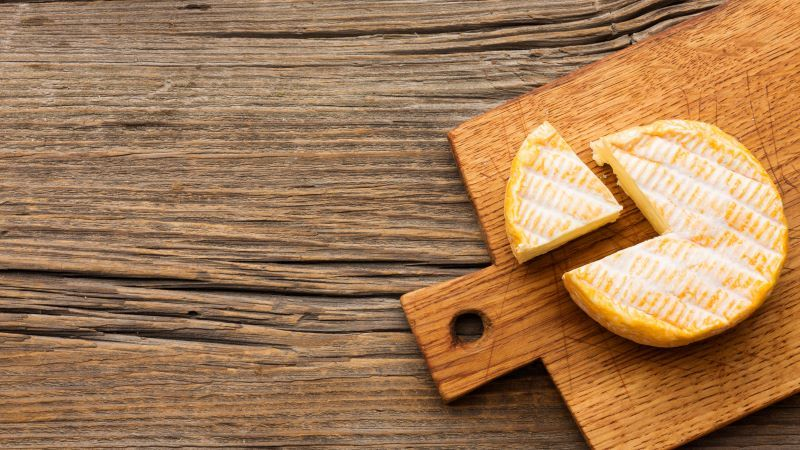 Chopping board with cheese on table
