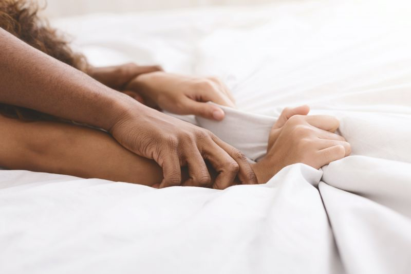 Close up of hands gripping bedsheets