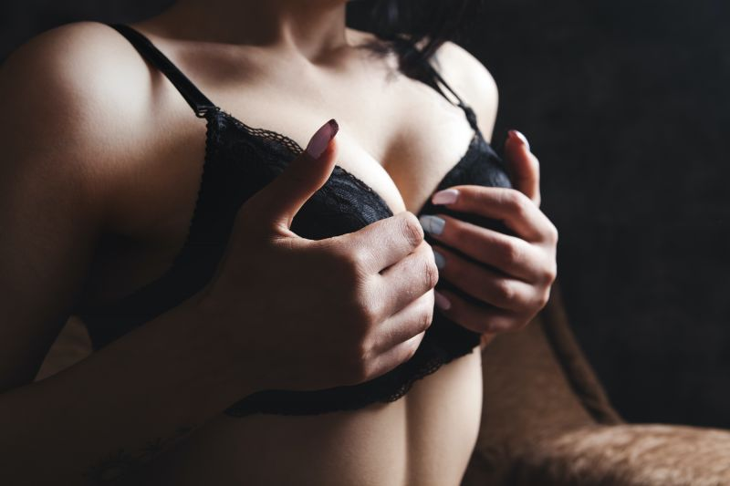 Close up of woman squeezing breasts in bra