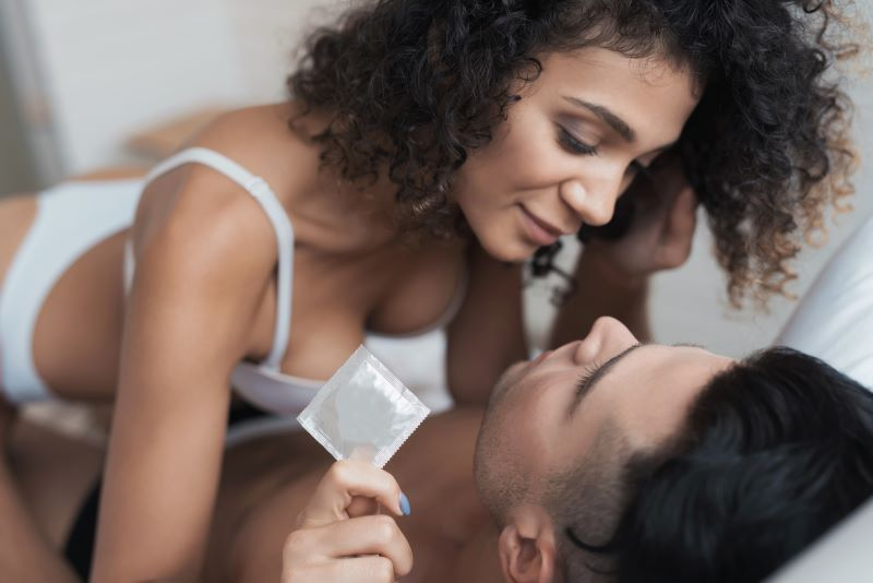 Couple having sex with woman holding condom