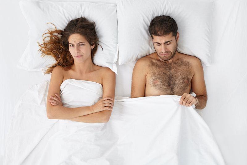 Couple in bed looking confused and unsatisfied