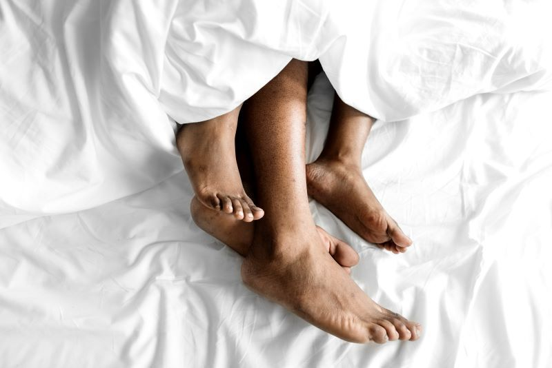 Couple in bed sleeping with feet showing
