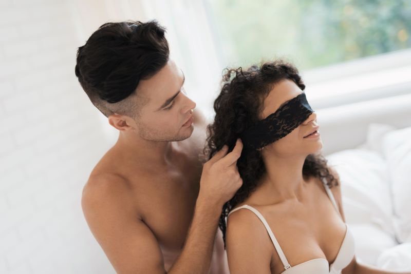 Couple in bed with blindfold kinky