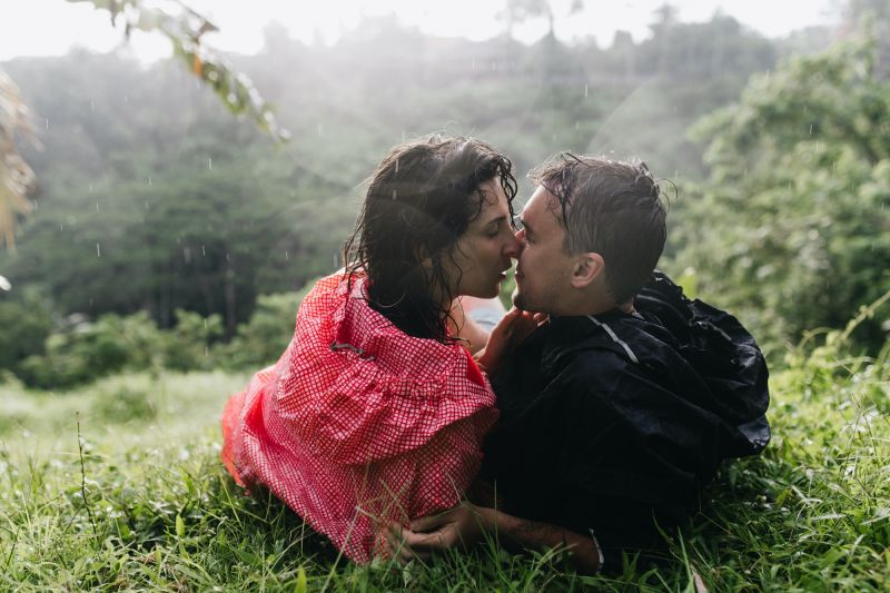 Couple kissing on grass in rain