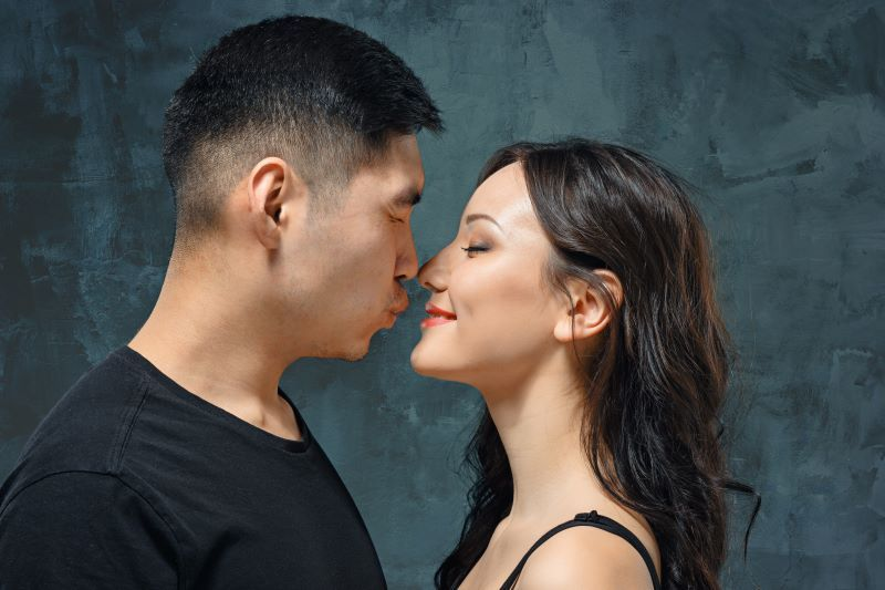 Couple leaning in for kiss and squinting