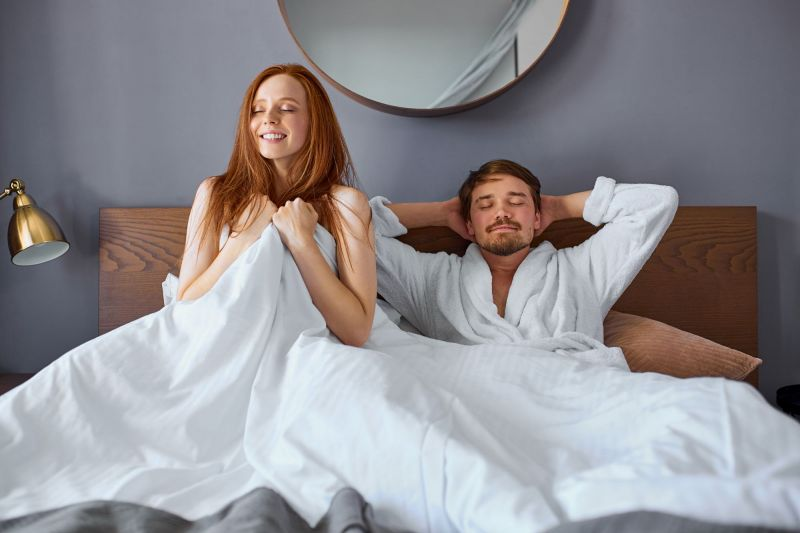 Couple smiling and stretching in bed