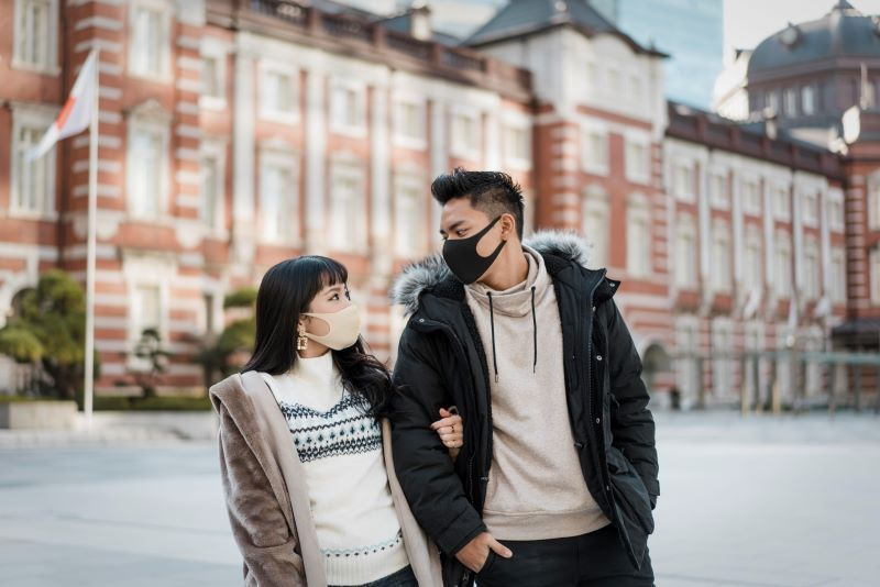 A couple walking outdoors wearing masks