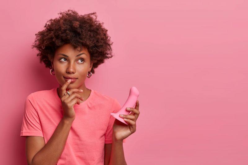 Curious woman holding pink dildo