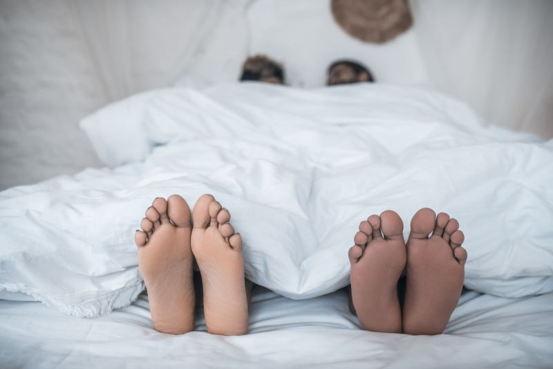 Couple's feet coming out of duvet