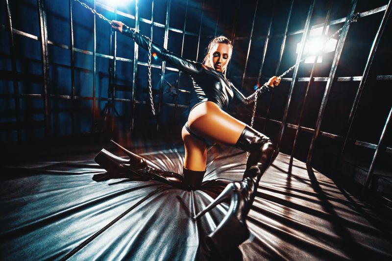 Female dancer in cage in BDSM outfit