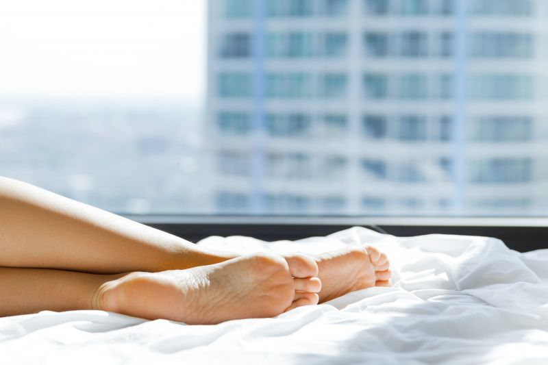 Female feet on bed with natural light