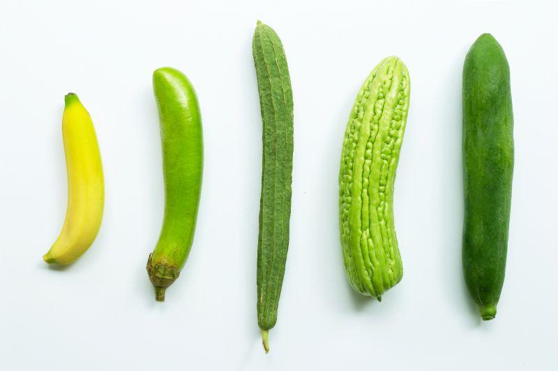Green phallic fruit and vegetables on white table