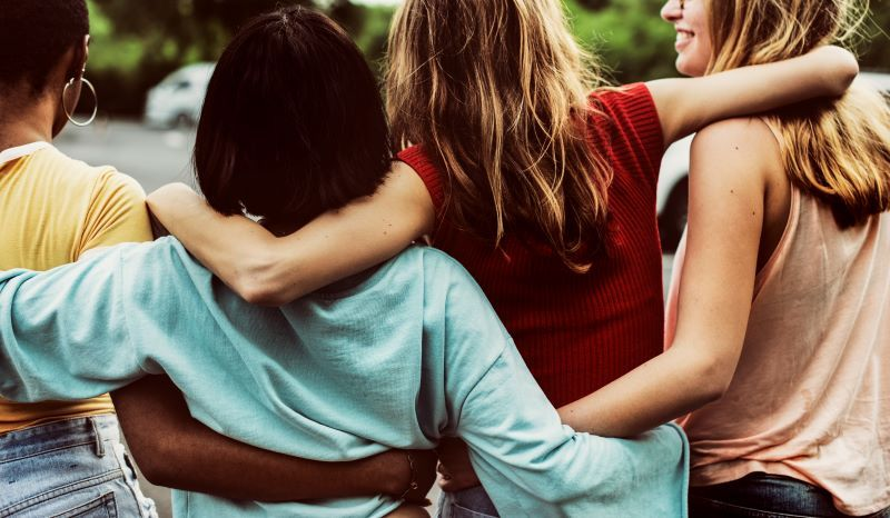 Group of female friends hugging and walking