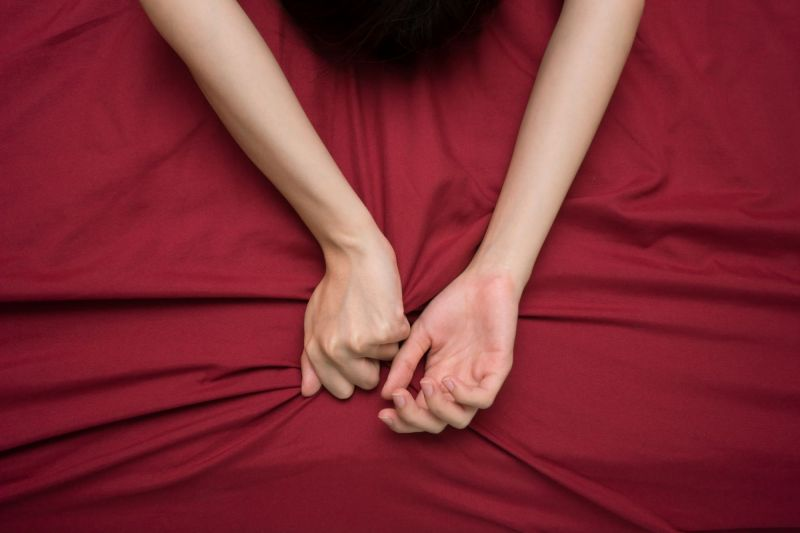 Hand grasping red bed sheet