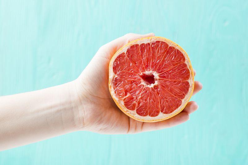 Hand holding half a grapefruit