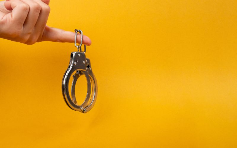Hand holding handcuffs on yellow background