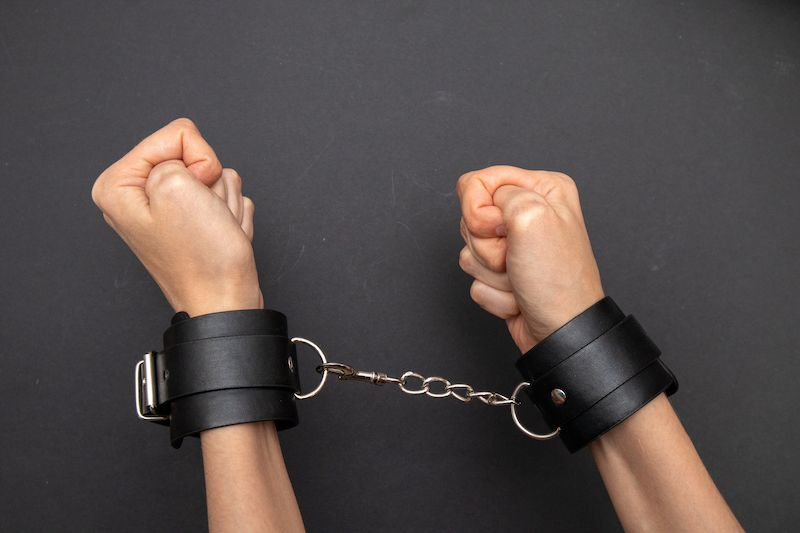 Hands in black leather BDSM cuffs