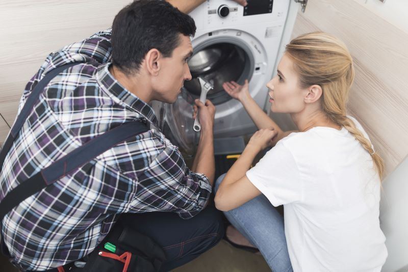 Handyman helps woman with washing machine