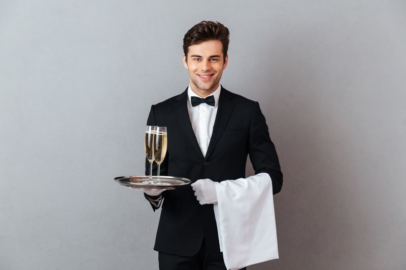 Attractive waiter holding champagne