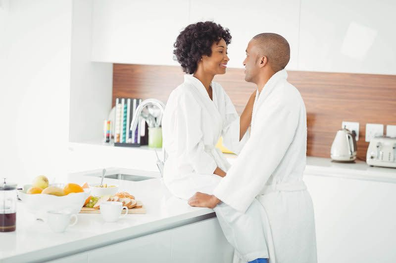 Happy couple in the kitchen at home in white gowns