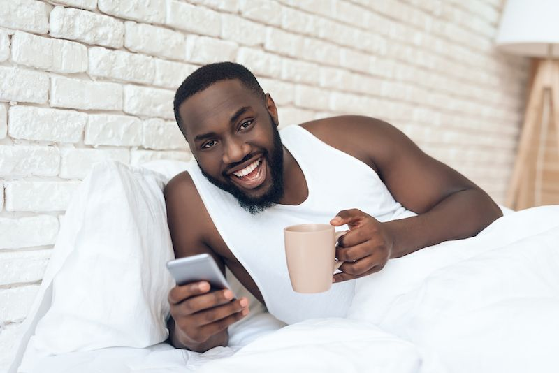 Happy man drinking coffee in bed