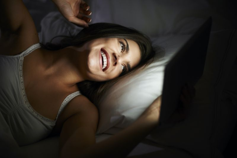 Happy woman on phone in bed at night