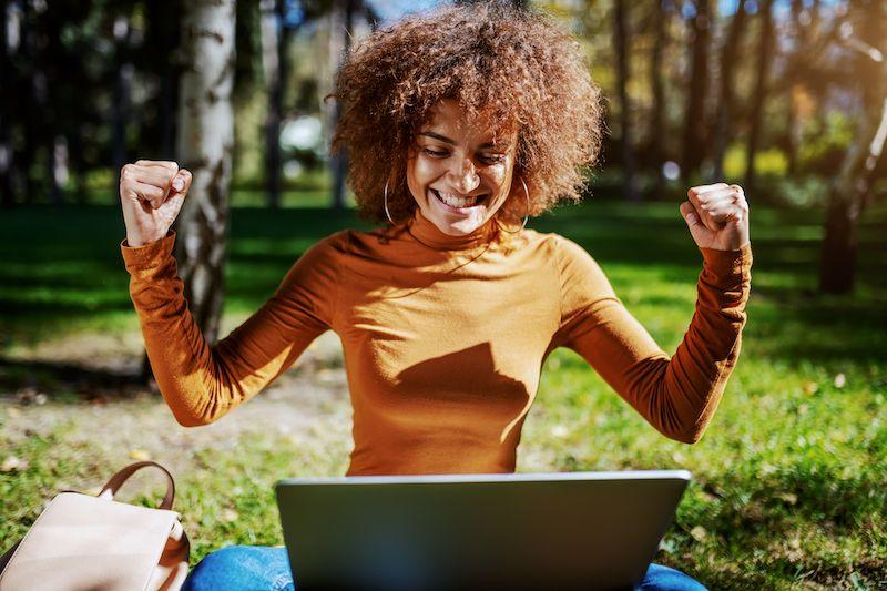 Woman sat outside on her laptop celebrating