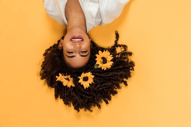 Happy woman with sunflowers in her hair