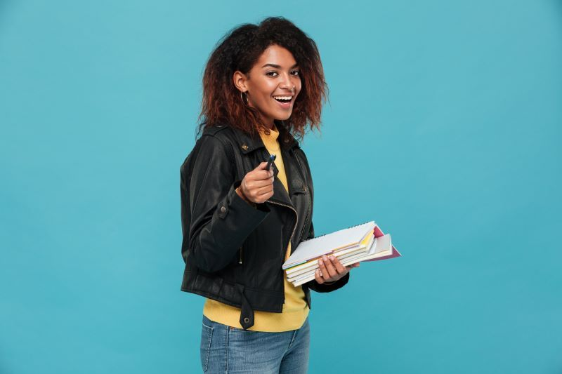 Happy young woman holding books