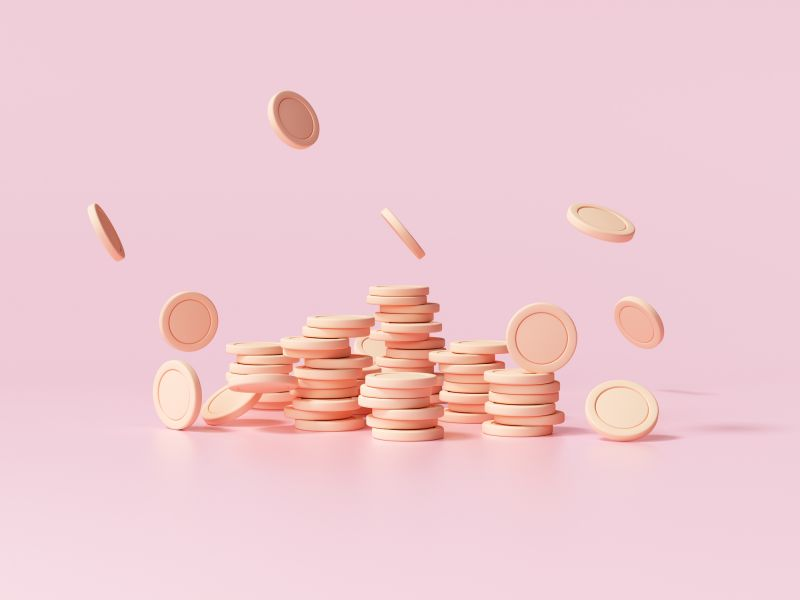 Stack of coins falling on pink background