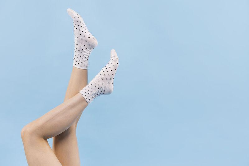 Woman's legs held upwards showing socks