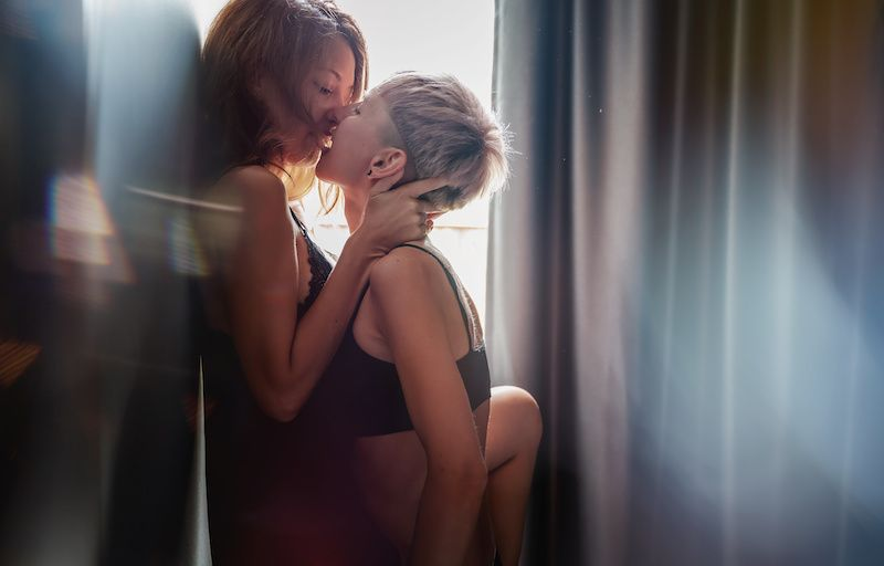 Lesbian couple kissing passionately against a wall