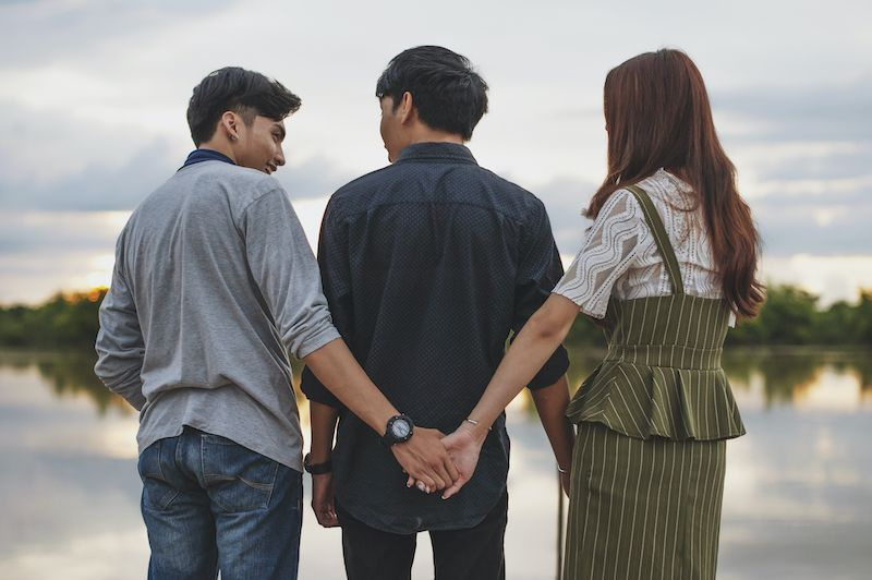Love triangle concept one woman holds hand of man behind back