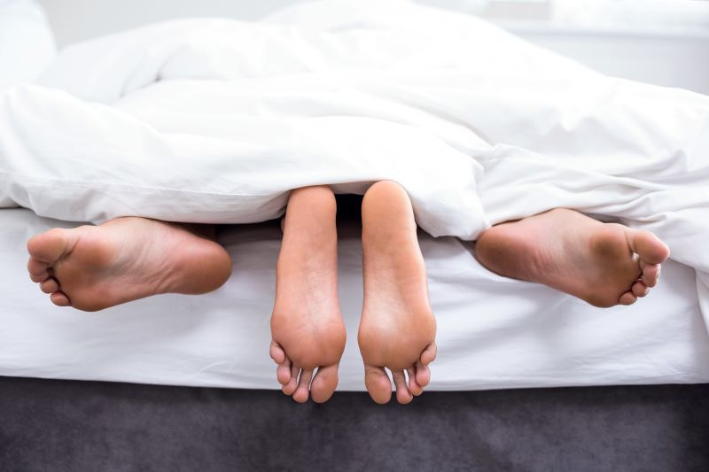 Couple in bed with feet showing