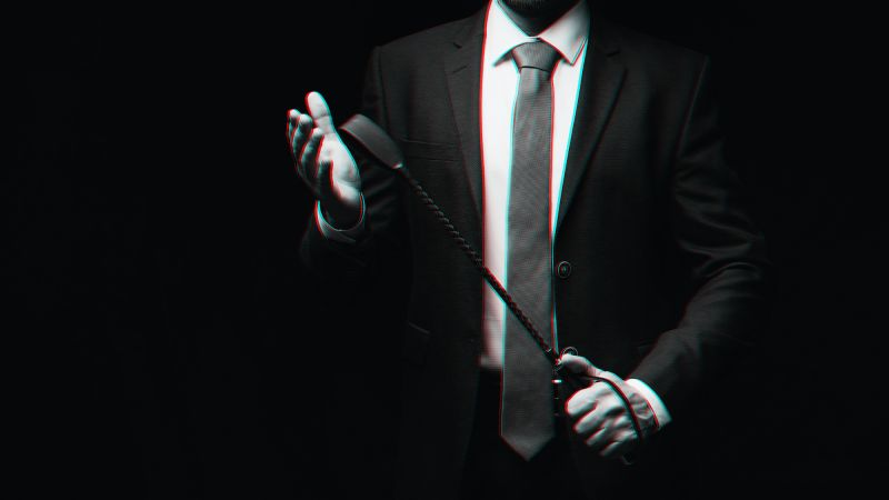 Male dom in suit holding leather whip