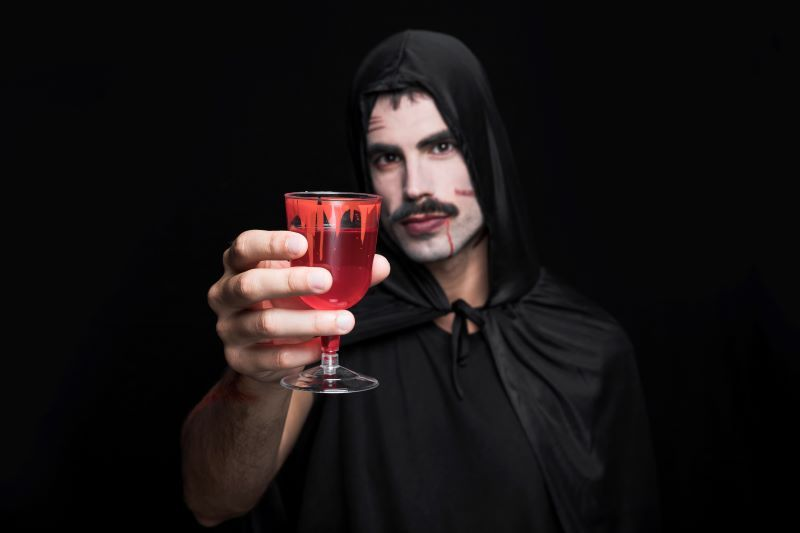 Man dressed as vampire holds up a drink