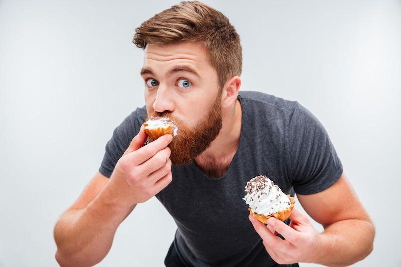 man eating cupcakes in a sexy way