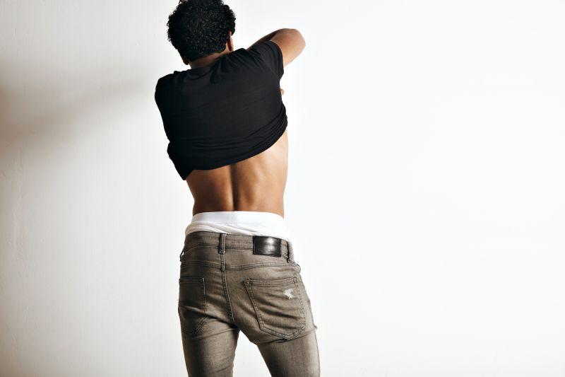 Man facing wall removing top
